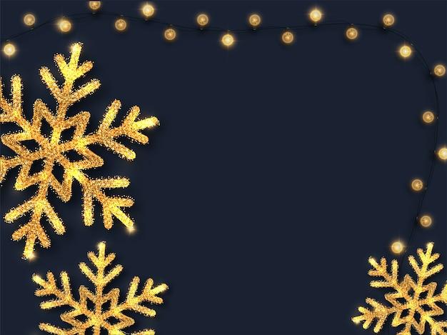 Flocons de neige scintillants dorés et guirlande d'éclairage décorée sur fond bleu