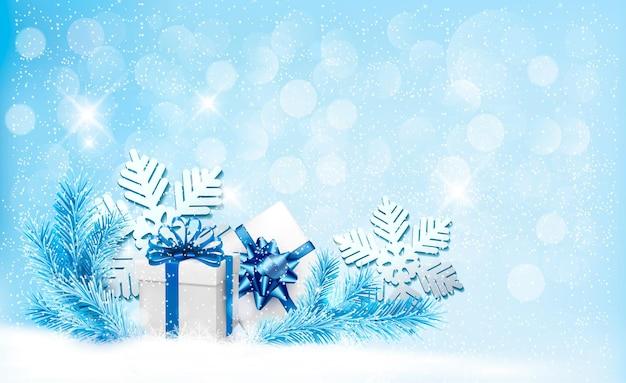 Fond bleu de noël avec des coffrets cadeaux et des flocons de neige.