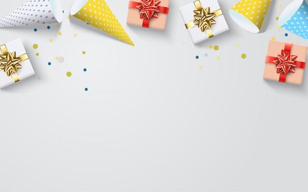 Fond de fête avec des chapeaux d'anniversaire colorés et des cadeaux