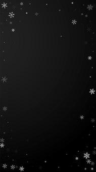 Fond de noël de chutes de neige clairsemées. flocons de neige volants subtils et étoiles sur fond noir. modèle de superposition de flocon de neige argenté d'hiver réel. illustration verticale resplendissante.