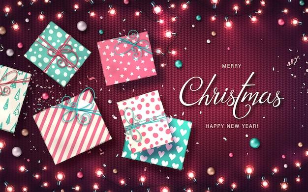 Fond de noël avec des lumières de noël, des boules, des coffrets cadeaux et des confettis. guirlandes lumineuses de vacances des ampoules led sur la texture tricotée. décorations de lampes colorées réalistes pour les cartes de nouvel an