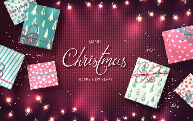 Fond de noël avec des lumières de noël, des boules, des coffrets cadeaux et des confettis. guirlandes lumineuses de vacances des ampoules led sur la texture tricotée pourpre