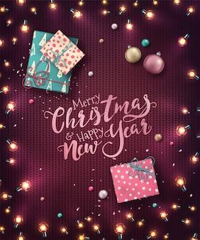 Fond de noël avec des lumières de noël, des boules, des coffrets cadeaux et des confettis. guirlandes lumineuses de vacances des ampoules led sur la texture tricotée