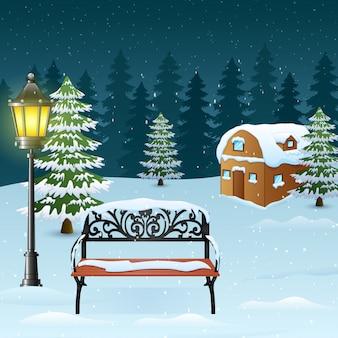 Fond de nuit d'hiver avec lampadaire et banc devant la maison enneigée