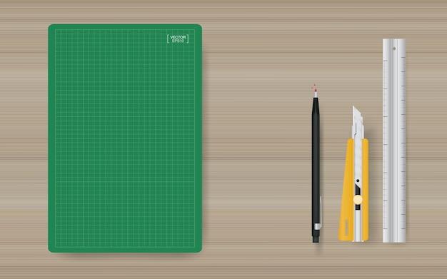 Fond d'objet de bureau de tapis de coupe vert avec règle, cutter et crayon sur bois.