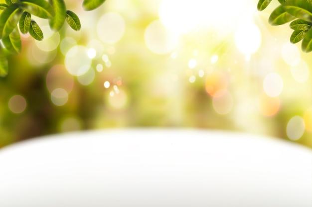 Fond de paillettes avec table blanche et éléments de feuilles vertes