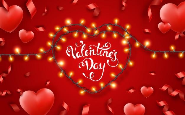 Fond de saint valentin avec des coeurs rouges, des rubans, des lumières et du texte .. décoration d'éclairage en forme de coeur festif de saint valentin