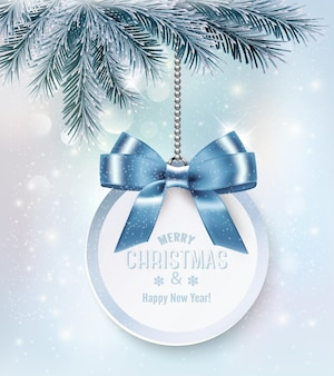 Fond de vacances de noël avec une carte-cadeau et un arc bleu.