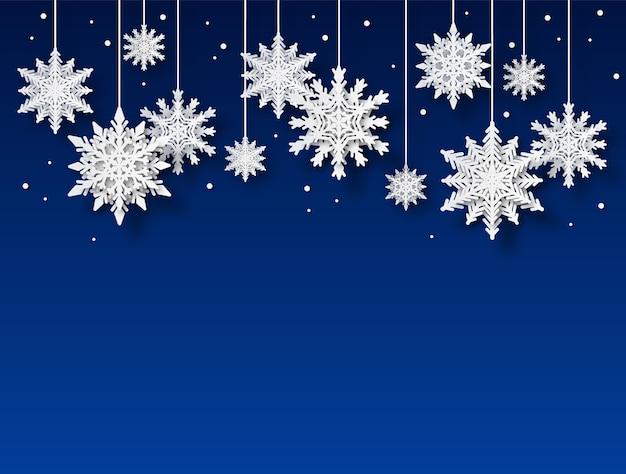 Formes de flocon de neige blanc papier découpé sur fond bleu