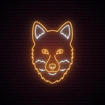 Fox au néon lumineux sur fond de mur de brique sombre.