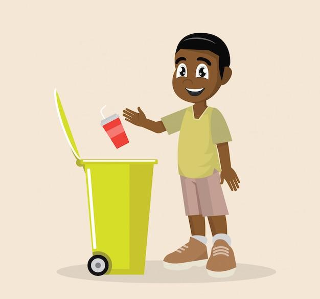 Un garçon africain met ses déchets en plastique dans une poubelle de recyclage.