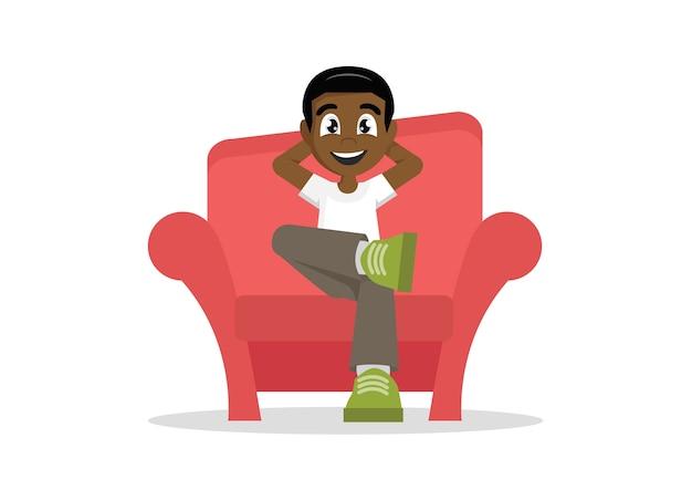 Garçon africain se détendre à la maison sur le canapé.