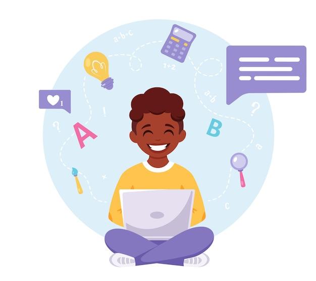 Garçon afro-américain étudiant avec un ordinateur en ligne apprenant à l'école