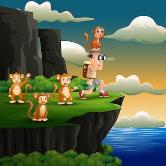 Garçon à l'aide de jumelles avec un singe sur la falaise