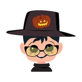 Garçon aux cheveux noirs, grands yeux et un large sourire heureux en chapeau avec tête de citrouille d'enfant avec visage joyeux...