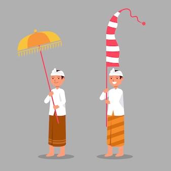 Un garçon balinais traditionnel apporte un parapluie et un long drapeau pour la cérémonie de rite