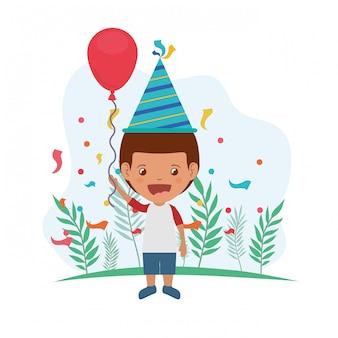 Garçon avec chapeau de fête et ballon d'hélium en fête d'anniversaire