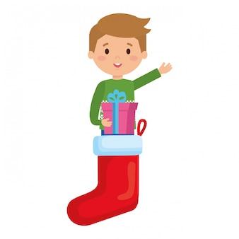 Garçon en chaussettes avec des vêtements d'hiver et cadeau