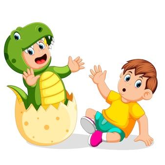 Garçon choqué quand son ami est sorti de l'oeuf et en utilisant le tyrannosaurus rex