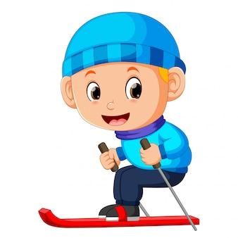Le garçon dans une veste bleue sur des skis