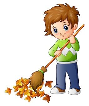 Garçon de dessin animé avec balai et feuilles d'automne