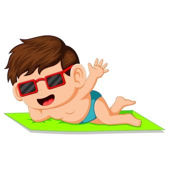 Garçon de dessin animé couché sur le tapis