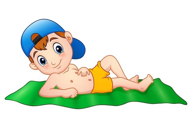 Garçon de dessin animé se trouvant sur le tapis