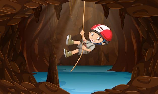 Un garçon explorant la grotte d'eau