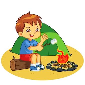 Garçon faisant le feu de camp et la guimauve de cuisson