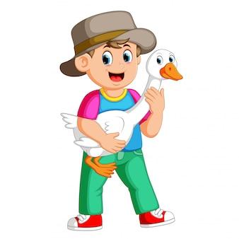 Un garçon de ferme tenant une oie