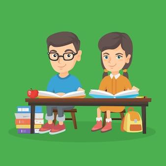 Garçon et fille assise à la table et en lisant.