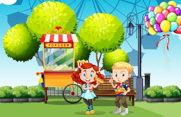 Garçon et fille mangeant dans le parc