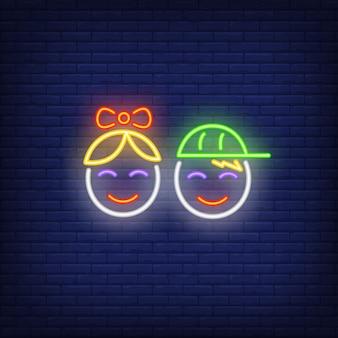 Garçon et fille souriante face à une enseigne au néon