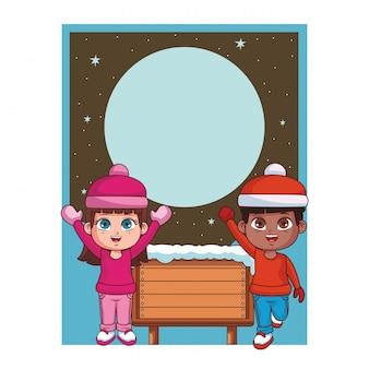 Garçon et fille avec des vêtements d'hiver et une carte de signe en bois