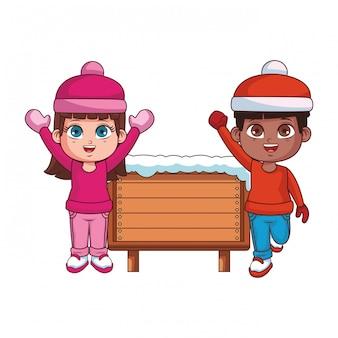 Garçon et fille avec des vêtements d'hiver et panneau en bois