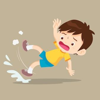 Garçon glisse et tombe sur le sol mouillé