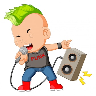 Un garçon habillé comme une rockstar chantant devant un haut-parleur