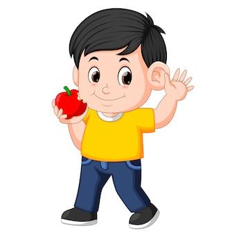 Garçon heureux mordre la pomme