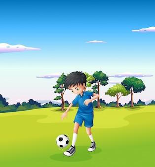 Un garçon jouant au football dans la forêt