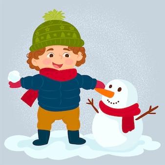 Garçon jouant avec un bonhomme de neige