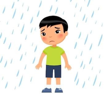 Garçon malheureux sous la pluie