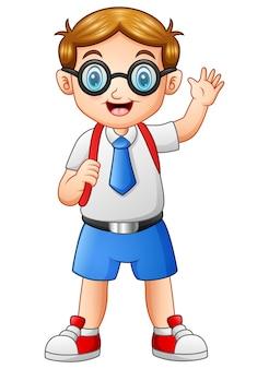 Garçon mignon dans un uniforme d'école agitant la main