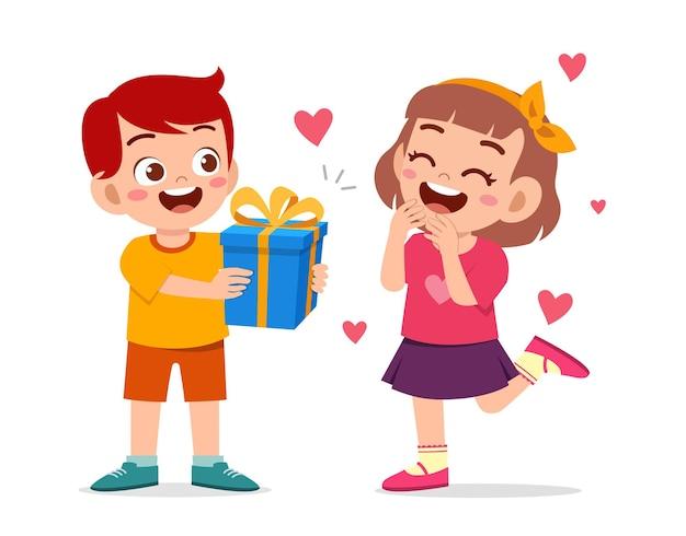 Un garçon mignon donne un cadeau à une petite fille pour célébrer son anniversaire