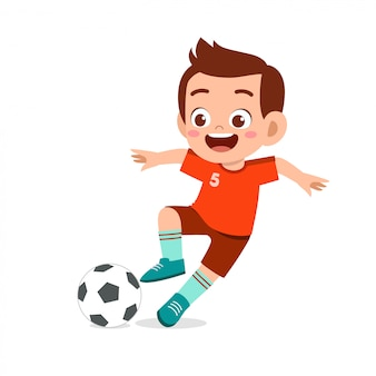 Un garçon mignon joue au football en tant qu'attaquant
