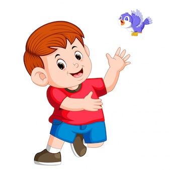 Garçon mignon jouer avec un oiseau