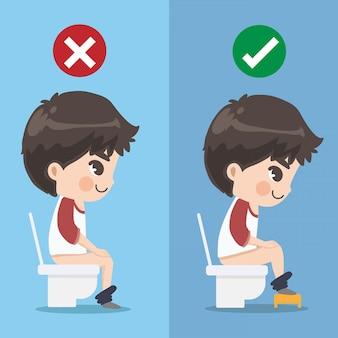 Le garçon montre comment s'asseoir correctement dans le siège des toilettes.