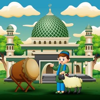 Garçon musulman avec un mouton devant la mosquée