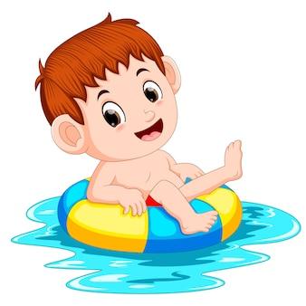Garçon nage dans la piscine avec le pneu de natation