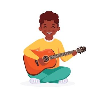 Garçon noir jouant de la guitare enfant jouant d'un instrument de musique