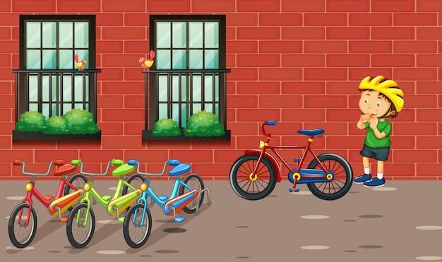 Garçon et de nombreux vélos par le bâtiment